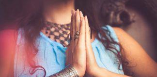 Frau hält Hände vor dem Herzen