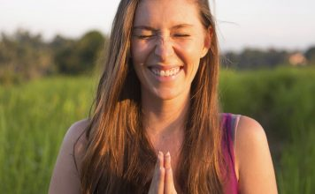 Eine junge Frau lacht und hält die Hände im Anjali-Mudra
