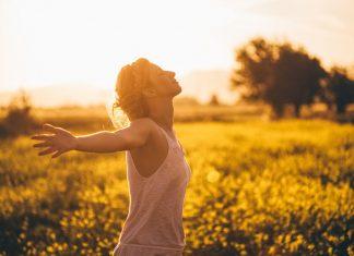 Frau auf einer Wiese in der Sonne