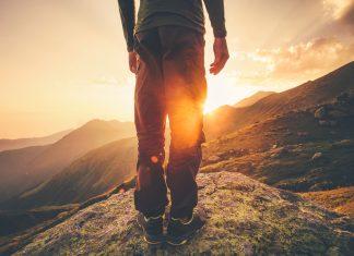 Mann steht auf einem Felsen.