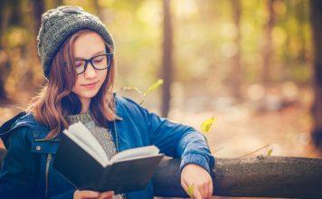 Junge Frau liest ein Buch im Wald