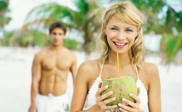 Frau trinkt aus einer Kokosnuss