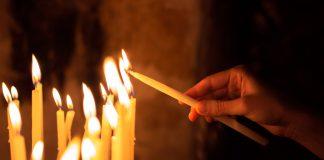Frau zündet Kerzen an