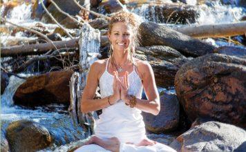 Frau im Lotussitz auf Stein im Fluss