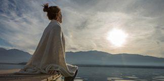 Frau sitzt an See und genießt Stille