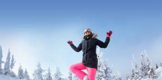 Frau übt Yoga im Schnee