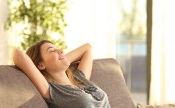 Frau sitzt entspannt auf Couch