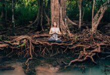 Frau meditiert unter Baum