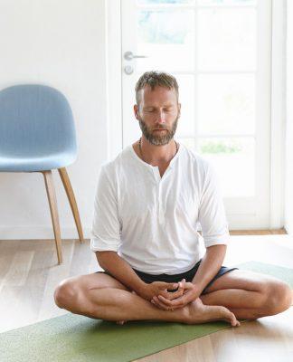 Mann auf einer Yogamatte