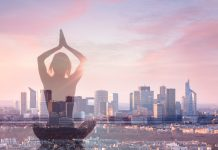 Frau meditiert vor Großstadt-Kulisse