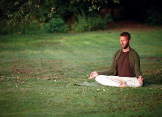 Mann meditiert auf einer Wiese