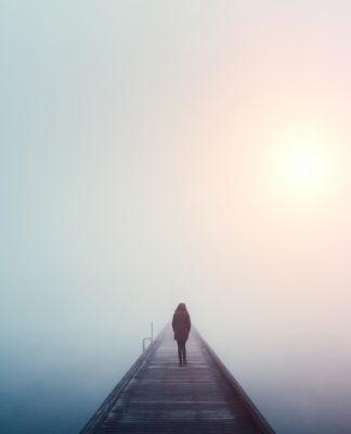 Frau geht über eine Brücke im Nebel