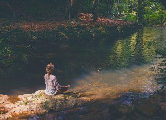 Frau meditiert am Wasser