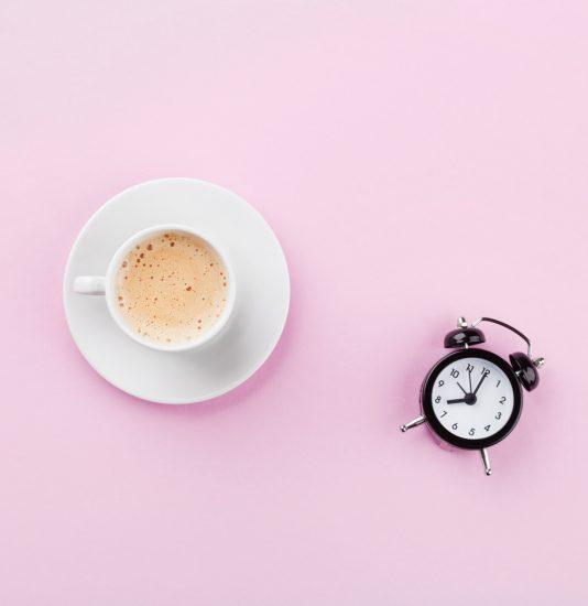 Kaffee und Uhr auf Tisch