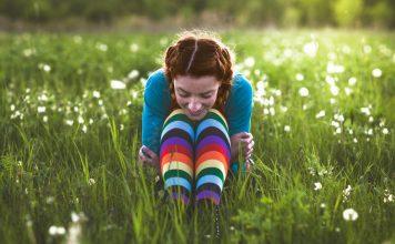 Frau sitzt auf Blumenwiese