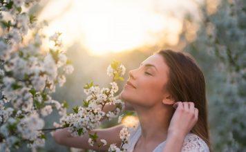 Frau riecht an Apfelblüte
